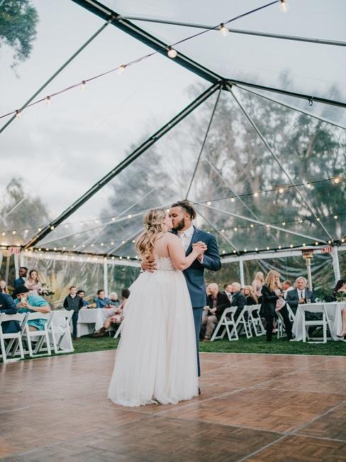 Couple de mariés entrain de danser sous une verriere