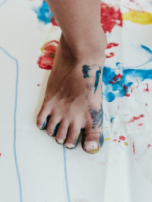 un petit pied d enfant tache de la peinture, pose sur une feuille de papier tachee de la peinture