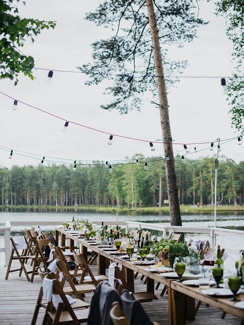 mariage en extérieur avec tables en bois au bord de l'eau