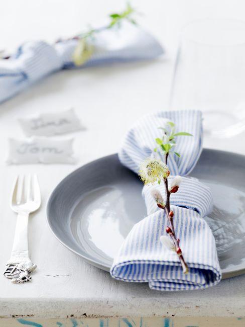 Décoration de table DIY avec des assiette bleu-grise et une serviette a rayures bleues, branche de fleurs jaunes et couverts argentes