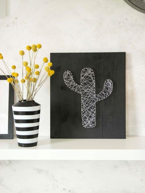 Tableau noir avec cactus sur etagere blanche avec des fleurs jaunes dans un vase raye noir et blanc