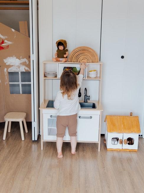 petite fille joue dans sa chambre montessori avec la cuisiniere pour enfants