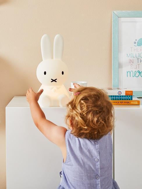 Petit enfant et veilleuse ne formede lapin sur commode blanche