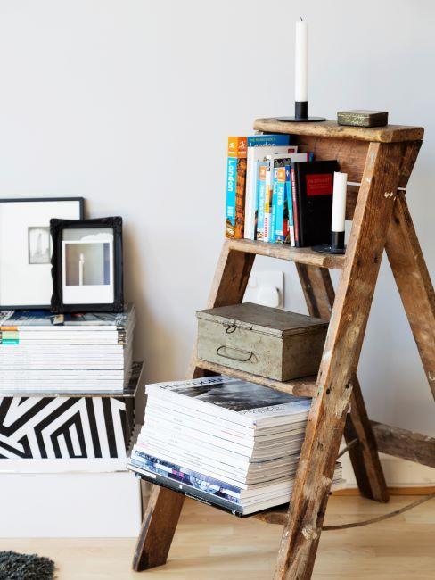 Echelle en bois servant d'etagere avec livres, magazines et boite de rangement
