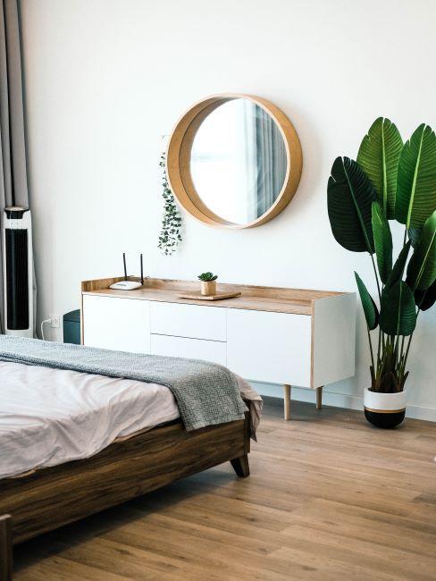 chambre avec lit en bois, meubles blancs et miroir rond