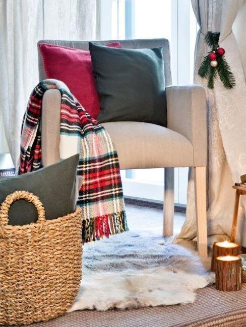 fauteuil beige avec coussins vert et rouge et plaid en tartan