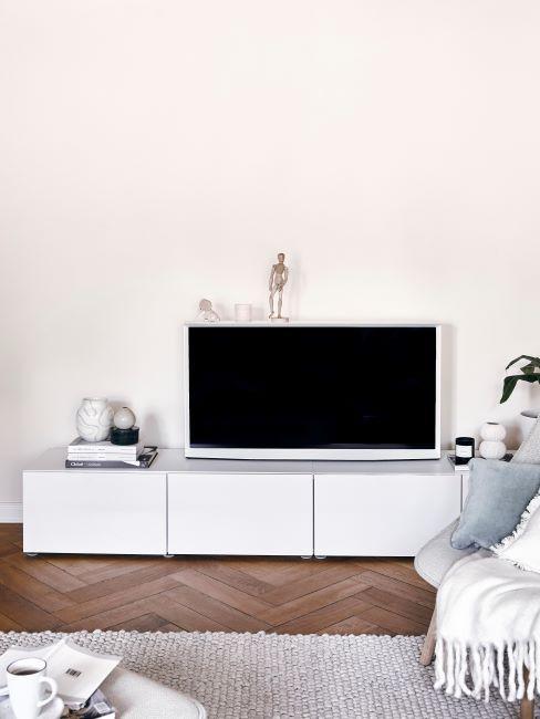 coin tv avec enfilade blanche, tapis beige, fauteuil crème, plaid blanc et coussin bleu