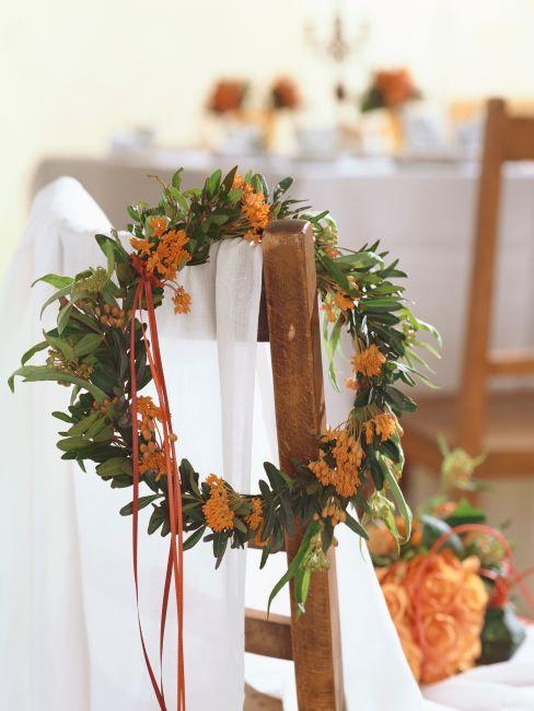 couronne floral orange suspendue sur une chaise en bois