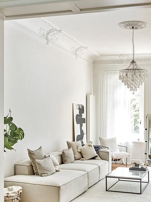 salon lumineux blanc avec canapé beige, lustre et moulures
