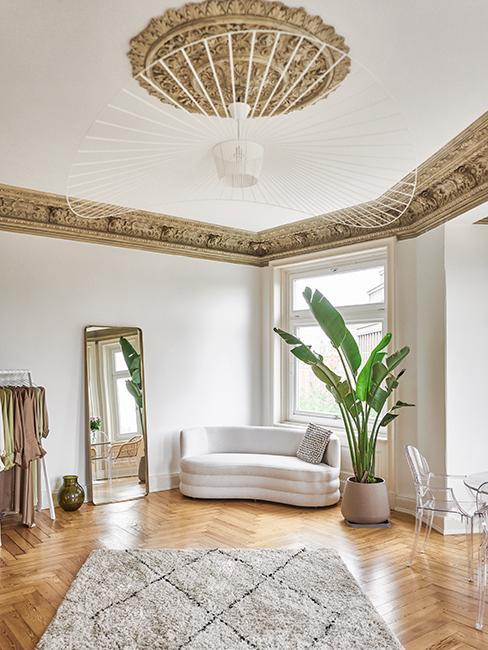 salon lumineux blanc avec canapé beige, lustre et moulures dorées