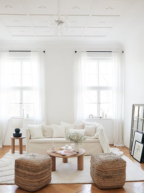 salon lumineux blanc avec canapé beige, pouf en osier et moulures