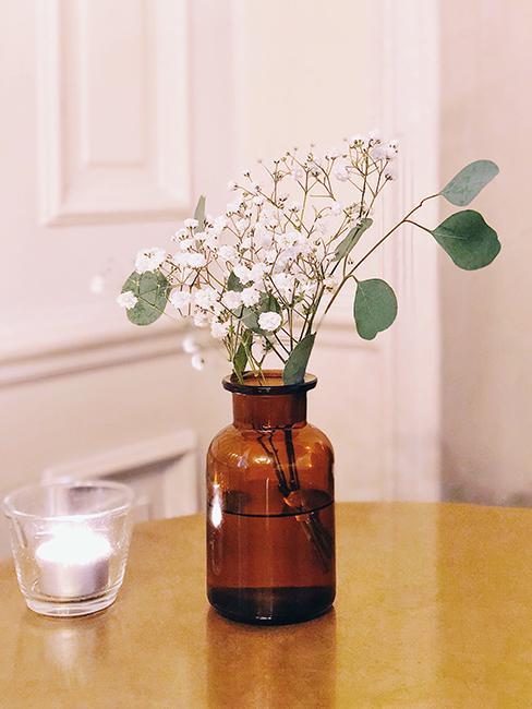 fleurs dans un vase sur une table en bois et un mur avec des moulures