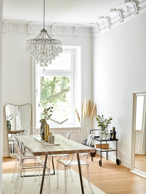 salle à manger avec table en bois et chaises transparentes, miroir doré, lustre et moulures