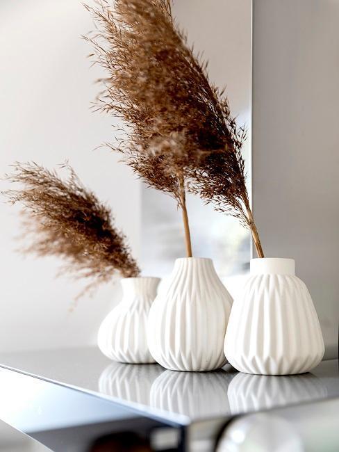 trois vases blancs sur une table avec de l'herbe de la pampa