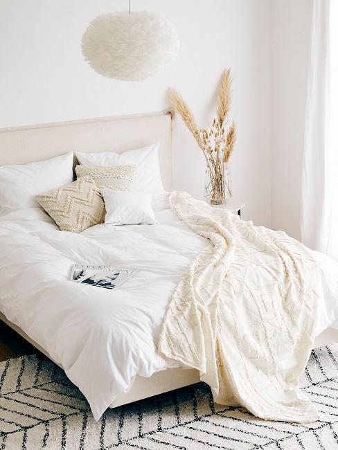 lit avec linge blanc, coussins et plaid beige, suspension nuage et herbe de la pampa