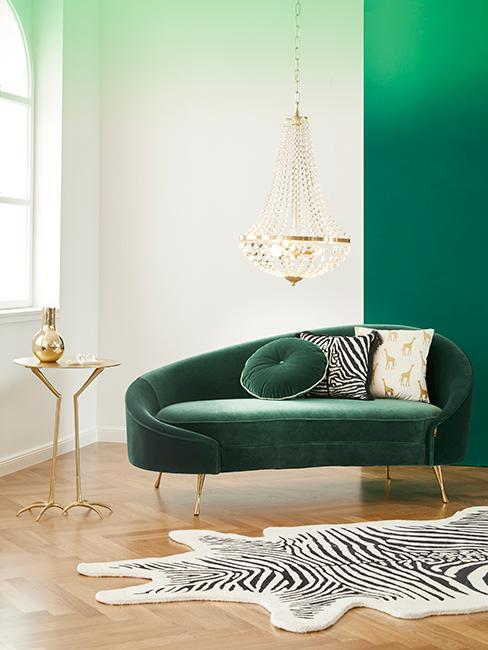 salon chic avec canapé vert foncé en velour, lustre et tapis zèbre