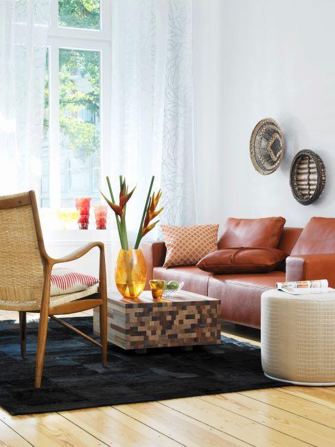 coin salon avec table basse a motifs, chaise tressee, canape en cuir marron, vase jaune