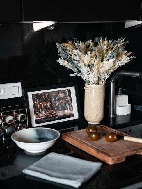 Cuisine noir mat avec planche à découper et vase beige