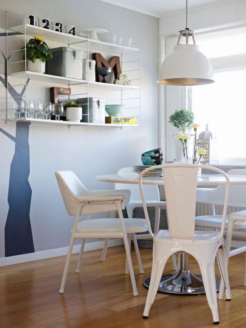 cuisine avec mur bleu gris, sticker en forme d'arbre, étagères murales, et chaises blanches