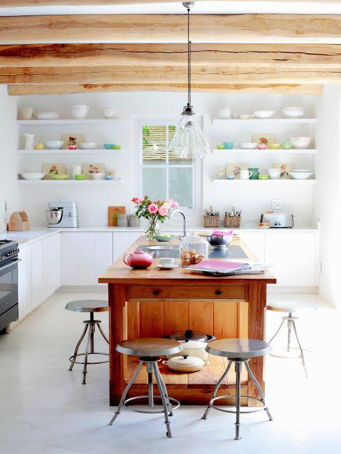 cuisine meubles blancs, ilot central en bois, poutres apparentes au plafond, tabourets, etageres murales