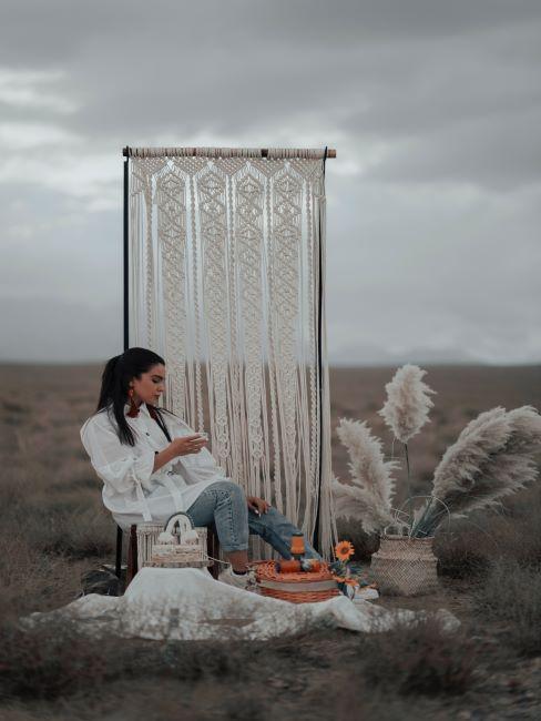 une femme assise à l'extérieur dans un desert, long macramé en paravent, herbe séchée
