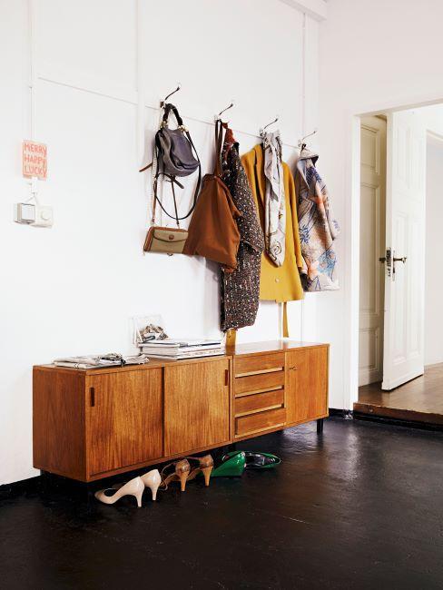 Grand couloir avec sol en parquet fonce et murs blancs, enfilade vintage en bois et porte-manteau