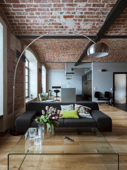 salon avec murs et plafond en briques, lampadaire arceau, canape noir