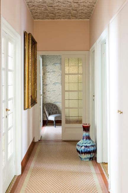 Couloir avec vase bleu posé au sol et miroir dor.