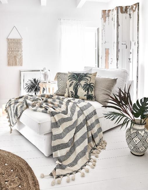 chambre boho avec plaid rayé, décoration murale en macramé et coussin palmier