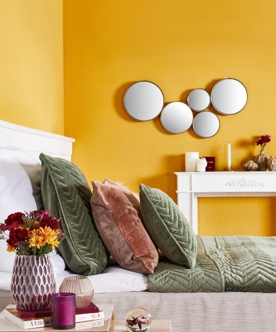 chambre moderne avec murs jaunes, décoration murale, parure couleur verte, vase avec fleurs