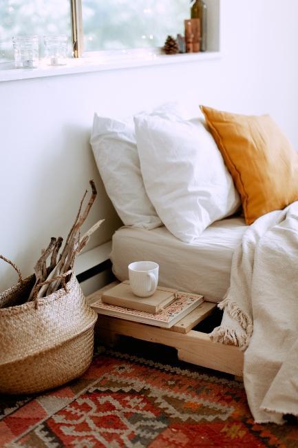 Chambre à coucher épurée avec tapis vintage, corbeille et coussin orange