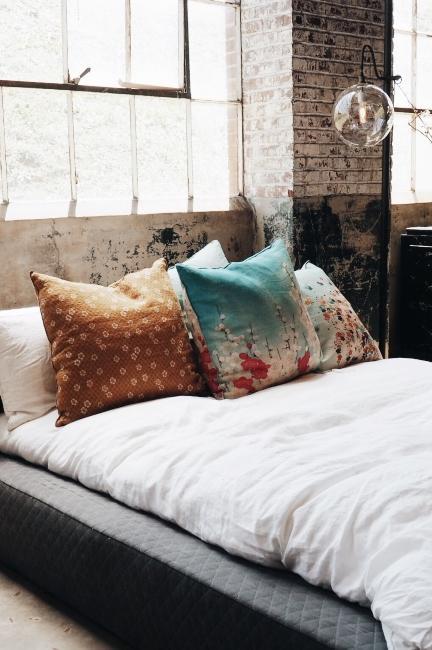 chambre industrielle dans loft avec parure de lit blanc et coussins à motifs