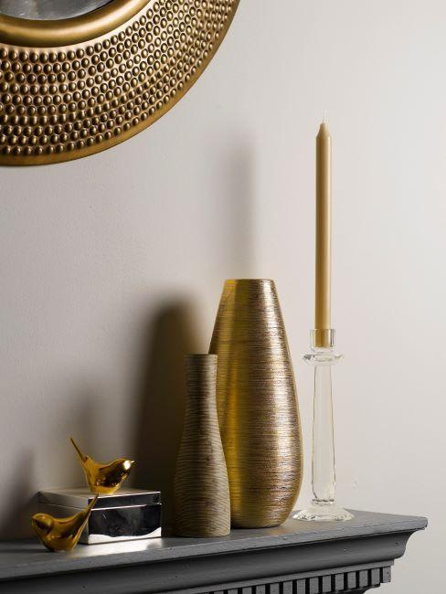 étagère noire avec déco dorée, miroir rond en métal, vase en métal brossé et chandelier avec bougie