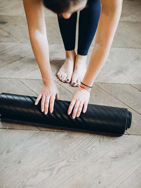 Femme entrain de dérouler un tapis de yoga