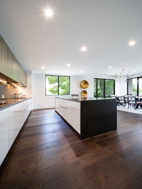 grand cuisine moderne avec sol en bois foncé, ilôt et meubles minimaliste