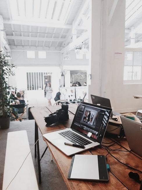 grand espace bureau avec murs blancs, meubles en bois et métal de style épuré et industriel