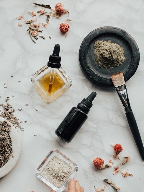 huiles essentielles, poudre, pinceau et fleurs séchés sur nappe blanche