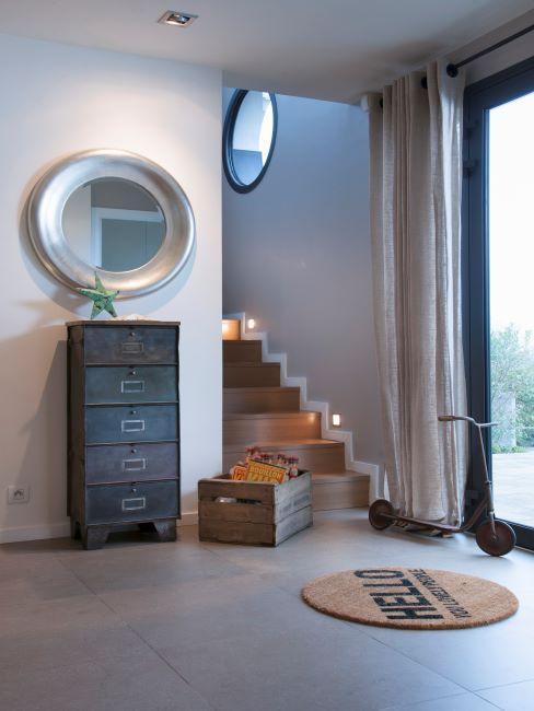 miroir rond, cadre argenté, épais, entrée minimaliste, style moderne, commode en bois, petit tapis rond, cage d'escalier