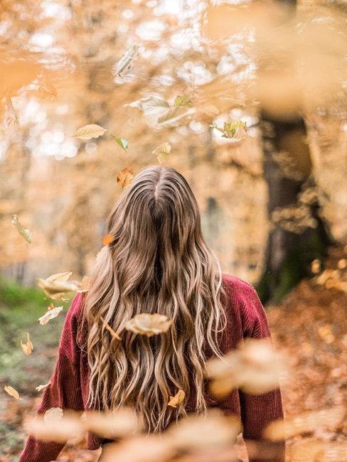jeune femme se promenant dans un parc en automne