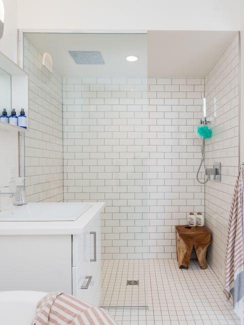 salle de bains à carreaux crème, meuble blanc, douche et tabouret en bois