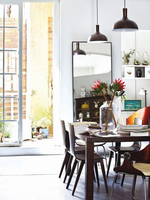salle à manger avec miroir, meuble en bois foncé, fleur et suspensions de style industriel