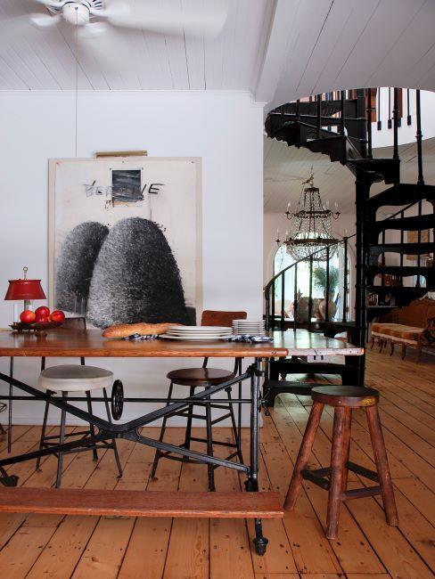 salle à manger dans un loft avec escalier industriel en fer, table en bois, tabouret récup vintage