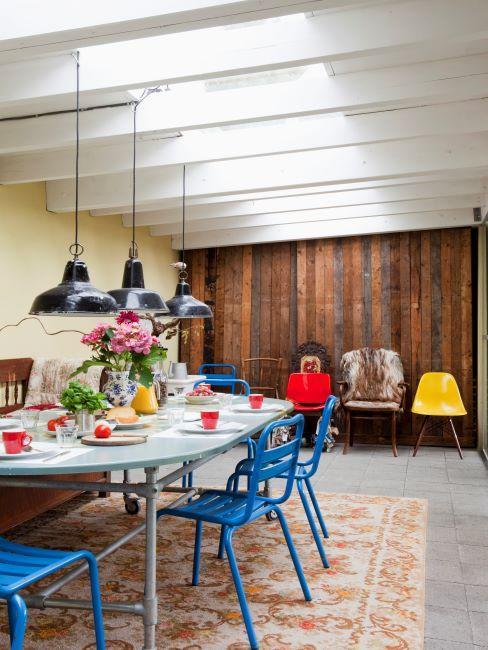 salle à manger avec murs en bois, suspensions industrielles, tapis oriental vintage et chaises bleues
