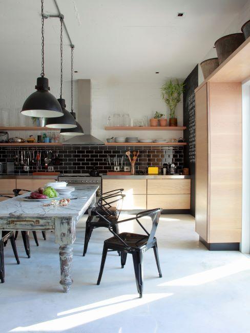 cuisine ouverte industrielle, meuble en bois clair, suspensions et chaises en métal vintage, table en bois
