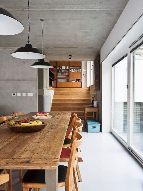 salle à manger avec murs en béton, grande table et chaises en bois, suspensions industrielle et grande fenêtre-véranda