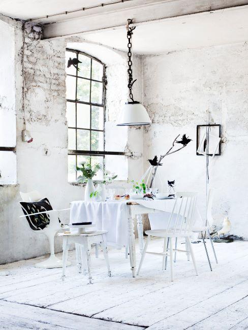 salle à manger dans une pièce aux murs de briques peints en blanc, suspension industrielle et mobilier blanc