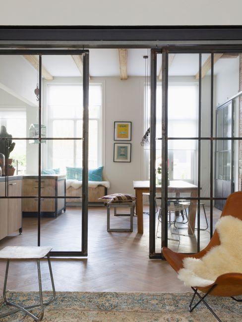 porte vitrée séparant le salon, fauteuil en cuir marron avec peau synthétique blanche dessus, grandes fenêtres