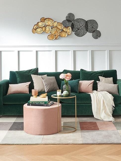 salon moderne style mid-century avec canapé en velours vert, pouf rose, table basse doré avec plateau en marbre et accessoires design