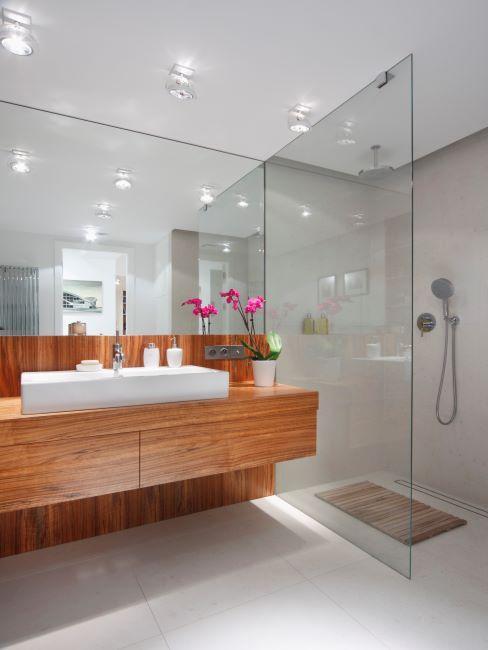 salle de bain avec douche moderne, grand miroir et vasque sur mobilier en bois
