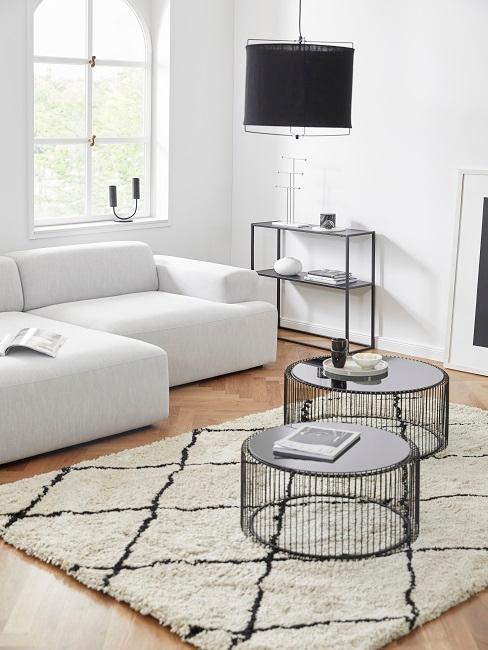petit salon avec canapé L, petites tables basses rondes noires et tapis moelleux